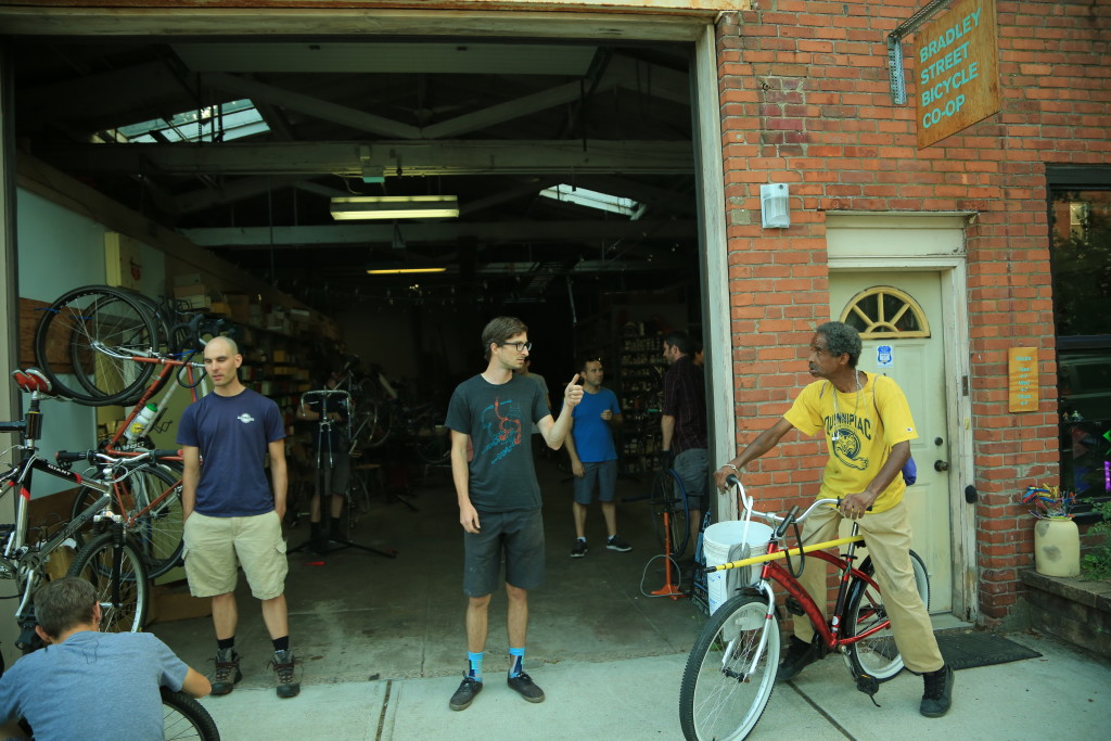 John Martin (center), the Bradley Street Bicycle Co-op's founder, and Joe Comfort (right), a regular, outside the shop. (Credit to Will Reid)